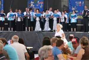 """Auf der Zentralbühne während des Internationalen Festes: Offenburger Chor der Deutschen aus Russland """"Jungbrunnen"""" unter der musikalischen Leitung von Anton Bittel (rechts)."""